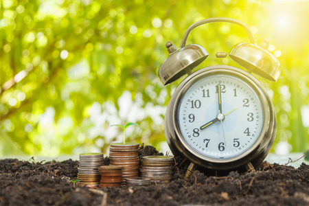 Alarm clock and money,coins stack and alarm clock on background,finance concept,business background and selective focus. Stock Photo