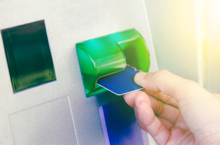 deposit slip: Hand inserting ATM card into bank machine to withdraw money,Hand of woman with credit card, using a ATM,finace background,business background and selective focus.