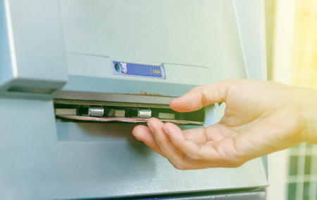 pin entry: ATM machine withdrawing money,Close-up Of Person Withdrawing Money From Atm Machine,finance concept,business background and selective focus.