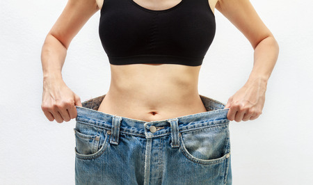 jeune fille adolescente nue: Young woman delighted with her dieting results on white background,A slim woman is showing how much weight she lost,healthy concept,healthcare content and selective focus. Banque d'images