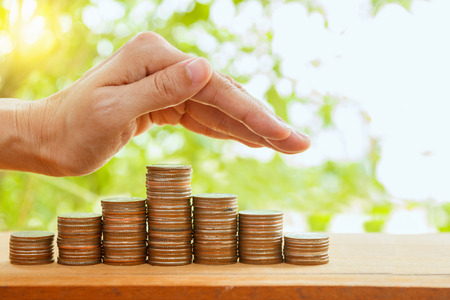 Hand putting coin on coins stack,Savings, Finance , Business Investment Growth Concept,Saving money concept,woman hand putting money coin stack growing business and selective focus.