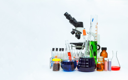 laboratory labware: science laboratory glassware and Microscope ,Group of laboratory flasks empty or filled with a clear liquid on blue tint scientific graphics background and their reflection on a table,science background,science glassware and selective focus.