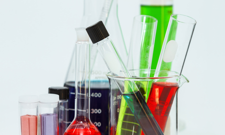 laboratory labware: science laboratory glassware,Group of laboratory flasks empty or filled with a clear liquid on blue tint scientific graphics background and their reflection on a table,science background,science glassware and selective focus.