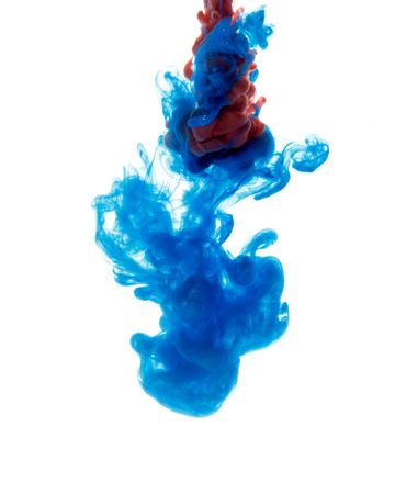 Colors dropped into liquid and photographed while in motion. Cloud of silky ink in water on white isolated background, an abstract banner. Stock Photo