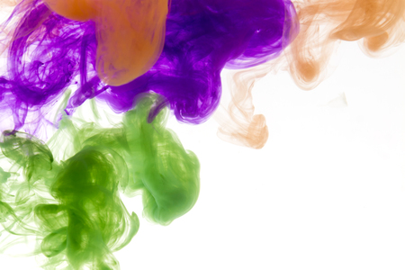 water splash isolated on white background: Colors dropped into liquid and photographed while in motion. Cloud of silky ink in water on white isolated background, an abstract banner. Stock Photo