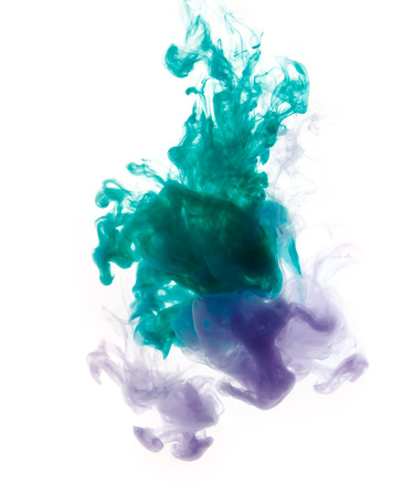 Colors dropped into liquid and photographed while in motion. Cloud of silky ink in water on white isolated background, an abstract banner. Imagens