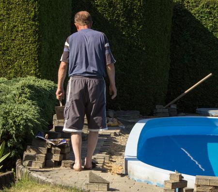 Building a garden pool. Laying paving blocks around the garden pool. Stock Photo