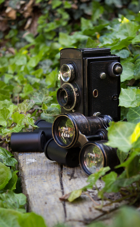 Retro camera and binoculars and photographic films in a garden with ivy.
