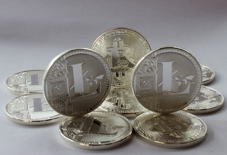 processors: On a white background are silver coins of a digital crypto  currencies - Litecoin and Bitcoin. In addition to the lying coin, there are one standing bitcoin and two standing litecoins.