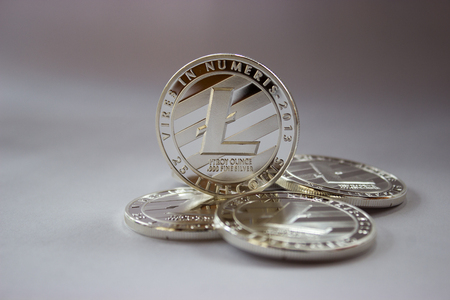 processors: On a grey background are silver coins of a digital crypto currency Litecoin.