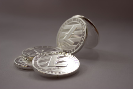 On a grey background are silver coins of a digital crypto currency Litecoin.