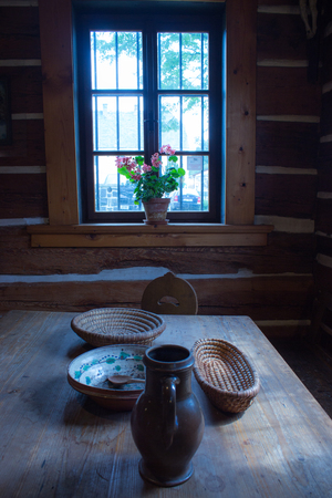 living room window: Room on the old weekend cottage. In the middle there is an oak table. On the table there is shallow flasket,  jug, bowl and a wooden spoon. There is a chair at the table. In the background is a window on which in pot are flowers. Stock Photo