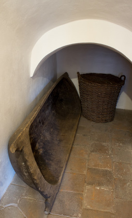 Wooden washtub that serves to prepare bread dough and a wicker basket in a niche. On the pavement.