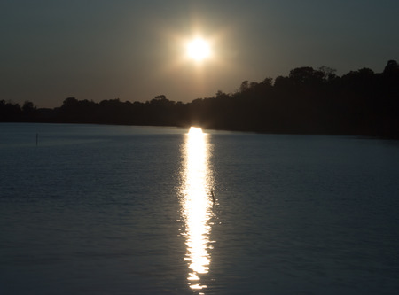 The setting sun is reflected in the water of the lake.