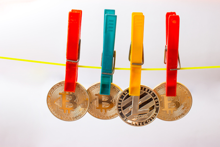 Colorful clothespins hold bitcoins and litecoin on a clothesline. The background is white.
