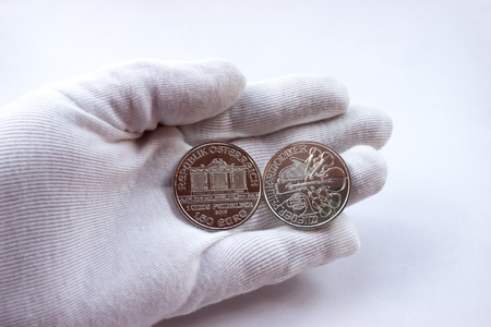 On a white glove are silver coins of an investment silver from an Austrian mint. Vienna Philharmonic Orchestra.