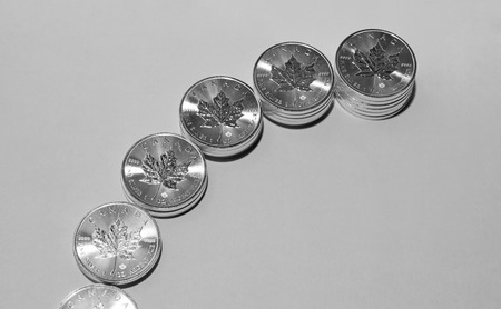 On a gray background are silver maple leaves coins of silver investment from Canadian Mint. Stock Photo
