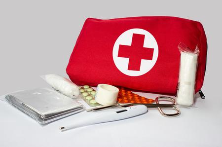 Eerste hulp kit - thermometer, schaar, patch, dressing, folie en drugs op de grijze achtergrond. Redactioneel
