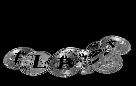 On a black background with free text space are silver coins of a digital crypto  currencies - Litecoin and Bitcoin. Stock Photo