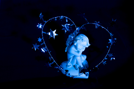 Figurine of a sleeping angel on a blue background. Around the cherub is a Christmas silver decoration in the shape of a heart with stars.