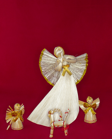Straw angels and reindeer on a red background. Christmas tree ornaments.