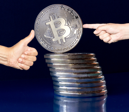 On a blue background are silver coins of a digital crypto  currency Bitcoin. In addition to the lying coins, there is standing bitcoin. On one side pushes finger in the bitcoin and on the other side supports his thumb. Stabilized value. Stock Photo
