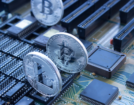 On a printed circuit board are silver coins of a digital crypto  currencies - Litecoin and Bitcoin. On a motherboard are standing bitcoin and litecoin.