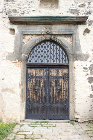 Entrance wooden gate to the castle with knockers and forging.  Stock Photo