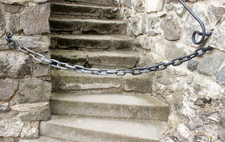 The chain that prevents the stair entry is located between the railing.Chain preventing entrance to the staircase. Standard-Bild