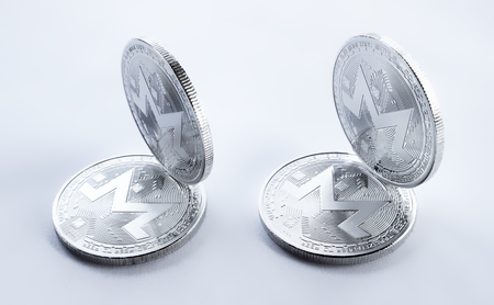 On a white background are silver coins of a digital crypto currency - monero. In addition to the lying coins, there are standing monero.