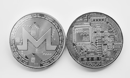 On a white background are silver coins of a digital crypto  currency - monero. The front and back sides of the silver coin monero. Stock Photo