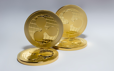 On the white background are gold coins of a digital virtual crypto currency - ripple. In addition to the lying coins, there is a standing ripple.