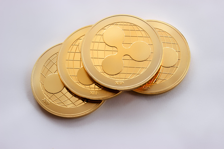On the black background there are four coins of a digital virtual crypto currency - ripple.