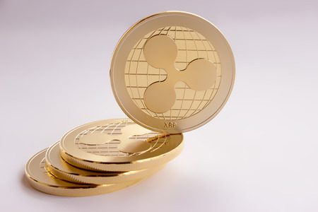 On the white background are gold coins of a digital crypto  currency - ripple xrp. On the inclined plane composed of three coins placed on one side, there is one gold coin standing.
