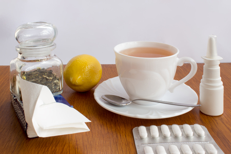 A cup of tea with saucer and spoon, lemon, medicines, a glass dose with tea, paper handkerchiefs, nasal drops. Everything against catch a cold on the wooden desk and white background. Stock Photo