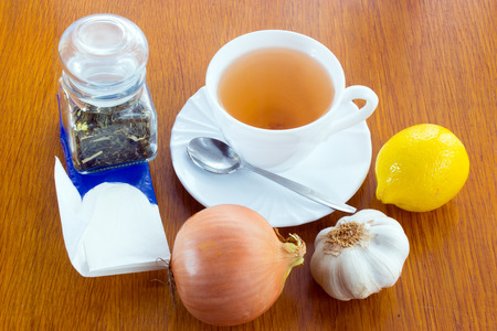 A cup of tea with saucer and spoon, lemon, onion, garlic, a glass dose with tea, paper handkerchiefs. Everything against catch a cold on the wooden desk. Stock Photo