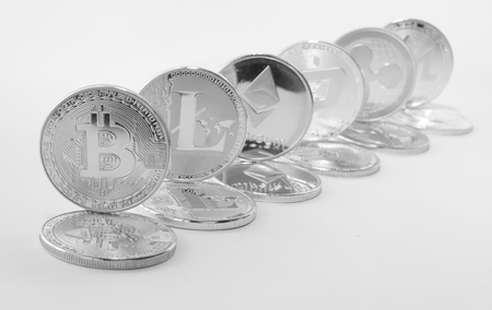 Silver coins of a digital crypto currency - litecoin bitcoin ethereum ripple dash monero. The coins stand on the lying coins of the same value. White background.