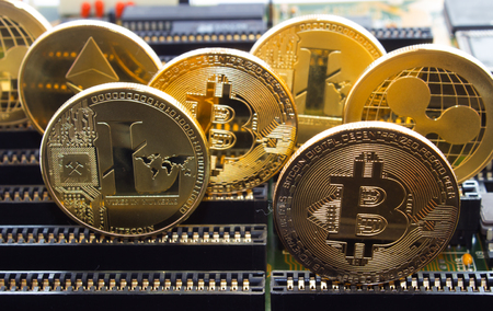 He and the motherboard in slots are standing gold coins of a digital crypto currency - litecoin bitcoin ripple.