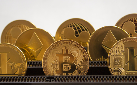 He and the motherboard in slots are standing gold coins of a digital crypto currency - litecoin bitcoin ripple. Stock Photo - 97452691