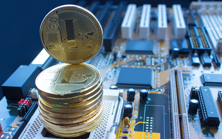 On a motherboard are gold coins of a digital crypto  currency - litecoin. The picture has a blue touch. Stock Photo