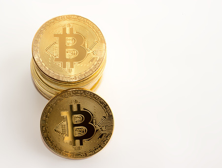 On a white background there are gold coins of a digital crypto currency - bitcoin. Zdjęcie Seryjne