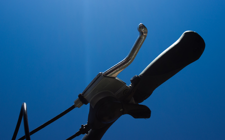 Detail of the bicycle brake and handle part. On the background is blue sky. Stock Photo