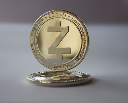 On a gray background are coins of a digital crypto  currency - zcash. In addition to the lying coin, there is standing zcash.