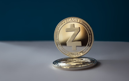 On a blue background are coins of a digital crypto  currency - zcash. In addition to the lying coin, there is standing zcash.