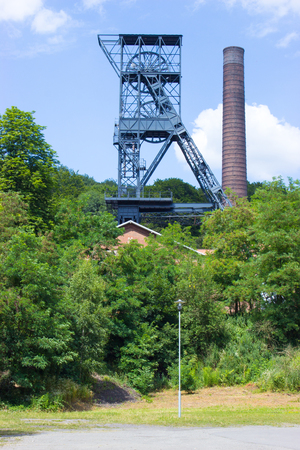 The mine tower for black coal mining Landek in city Ostrava in the Czech Republic. In the background is blue sky with white clouds. In foreground are trees and bushes and lamp.