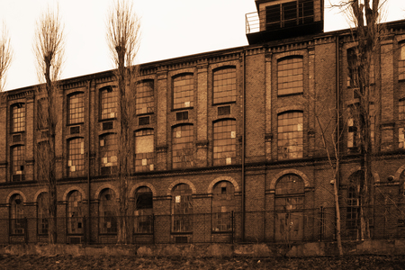 Old industrial derelict building in sepia color