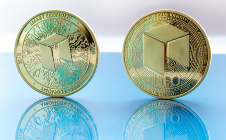 On a blue glass are coins of a digital crypto  currencies - neo and their reflection. Banco de Imagens