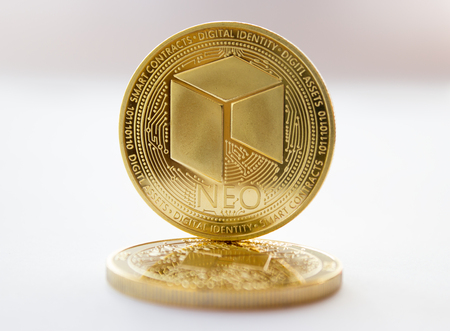 On a gray background are coins of a digital crypto  currencies - neo. In addition to the lying coin, there is standing neo.