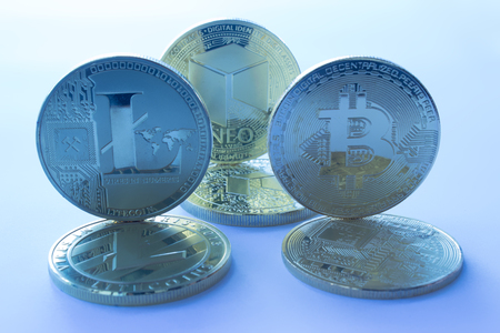 On a blue background are coins of a digital crypto  currencies - neo bitcoin litecoin. In addition to the lying coins, there are standing neo bitcoin and litecoin. Banco de Imagens
