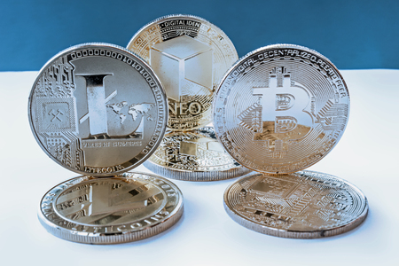 On a blue background are coins of a digital crypto  currencies - neo, bitcoin litecoin. In addition to the lying coins, there are standing neo bitcoin and litecoin.